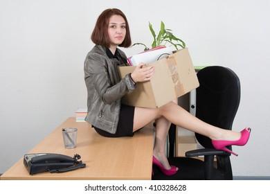 Upset business woman carrying office belongings after loosing job