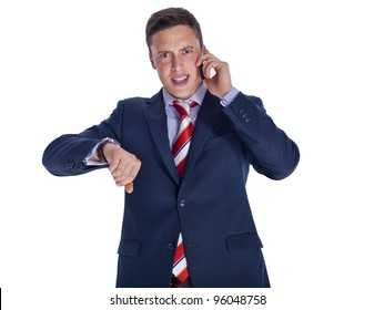 Upset businessman checking time while talking on the phone