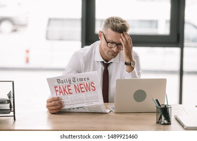 upset businessman in glasses holding newspaper with fake news