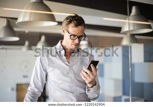 Upset businessman looking at his smartphone.