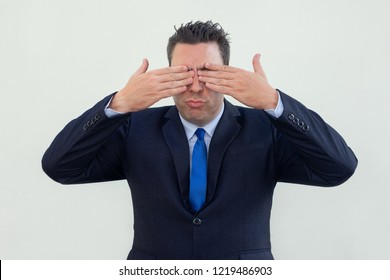 Upset businessman puckering lips and covering eyes with hands. Tired male executive rubbing eyes. Exhaustion concept