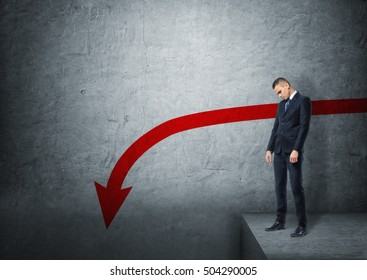 Upset businessman standing on the edge of abyss on the background of concrete wall with red arrow going down. Slump and recession. Stock market plunge.