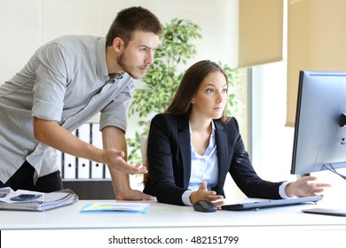 Upset businesspeople trying to work on line with a desktop computer looking at monitor at office
