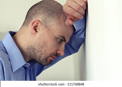 Upset caucasian man is leaning on the wall