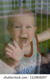 Upset Caucasian Toddler Baby Boy Cries Through Glass Window From Separation Anxiety Worries Woes At Daycare While Parent Leaves
