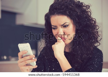 Upset confused young woman suing mobile phone reading text message