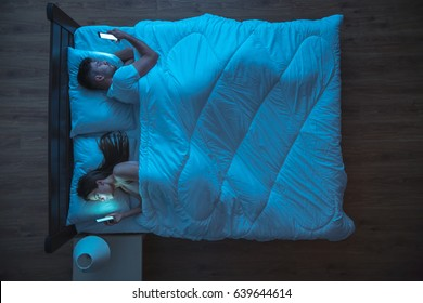 The upset couple with phone lie on the bed. night time. view from above