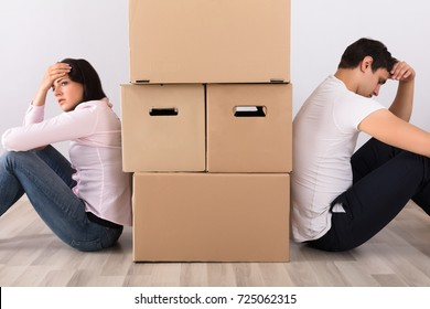 Upset Couple Sitting Back To Back Behind The Cardboard Boxes In Apartment