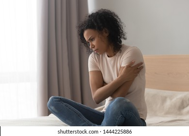 Upset depressed african woman feel hurt sad sit alone on bed, frustrated black girl thinking of loneliness, unwanted pregnancy having psychological trauma grieving troubled with problem in bedroom