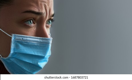 Upset depressed melancholy sad crying woman in protective mask with tears eyes during cancer illness, coronavirus outbreak, flu covid-19 epidemic. Difficulties and problems during disease. Copy space