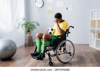 upset disabled african american sportsman in wheelchair holding football