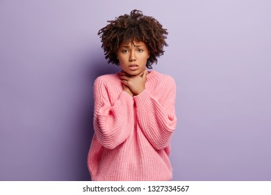 Upset discontent lady with dark skin, curly hair, keeps both hands on neck, suffers from asthmatic fit, wears oversized pink jumper, suffers from cough attack, poses indoor. Painful feelings in throat