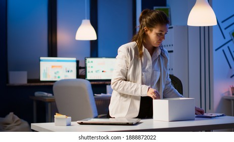 Upset dismissed woman employee putting her stuff in box from table at office as being fired. Unemployed packing things late at night. woman closing laptop and leaving workplace office in midnight