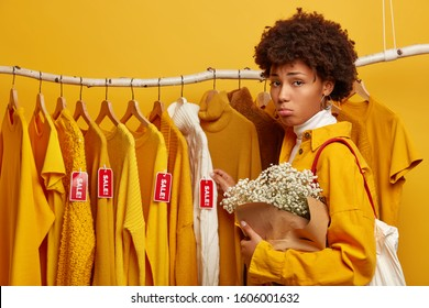 Upset dissatisfied woman purses lips, looks unhappily at new clothes on racks, has not enough money for paying purchase, chooses sweater on sale, carries beautiful bouquet, isolated on yellow wall