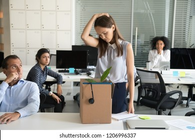 Upset female employee packing belongings in box, frustrated stressed girl getting fired from job ready to leave on last day at work, sad office worker desperate about unfair dismissal losing job
