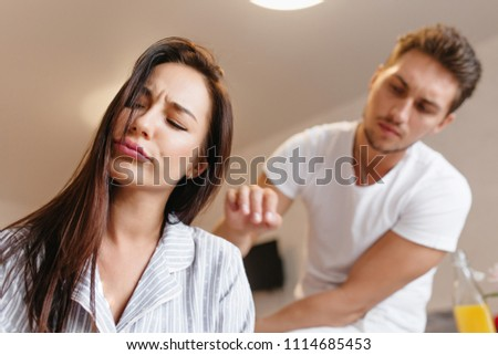 a1ec70e8b6 Upset female model in cute pajama posing with eyes closed while caucasian  man telling something.