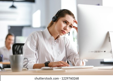 Upset frustrated young woman wearing microphone headset dressed in shirt sitting at her workplace at the office, working on computer