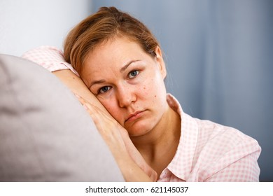 Upset girl with blond hair lonely sad at home sitting on couch