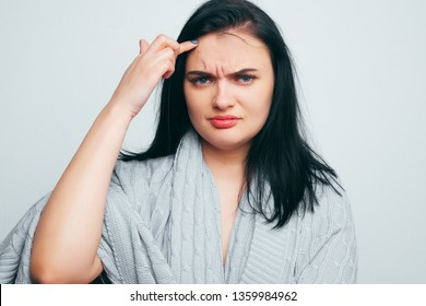 Upset girl in a gray robe indicates poor skin, age wrinkles, acne on a white and gray studio background. A woman is looking for flaws and age changes