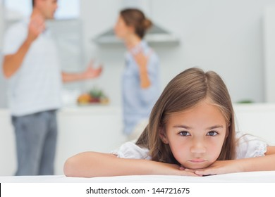 Upset girl listening to parents quarreling in the kitchen