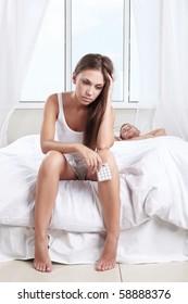 Upset girl with pills next to a sleeping man