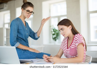 Upset girl in striped T-shirt thoughtfully aside while lady boss in eyeglasses scolding her in modern office
