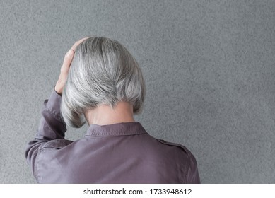 Upset gray-haired woman, holding her head with her hand, on gray background with copy space.