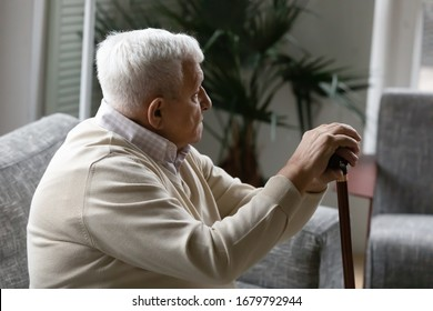 Upset grey haired old man sit on couch in living room alone holding wooden cane walking stick feels lonely thinking about life troubles and disability. Older people healthcare and nursing home concept