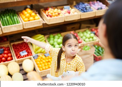 Upset grimacing daughter with pony tails complaining to mom and gesturing aside, she getting hysterical in organic food shop