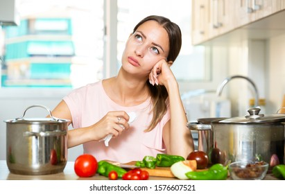 Upset housewife trying to cook vegetable soup at kitchen