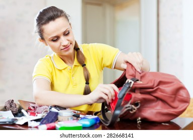Upset inconsiderate woman lost something and finding in handbag