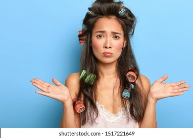 Upset indecisive young woman spreads palms with clueless dissatisfied expression, cannot decide what to wear today, dressed in nightgown, has curlers on long dark hair for making nice hairstyle
