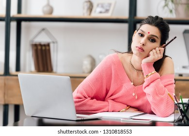 upset indian woman with bindi studying with laptop at home