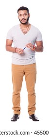 Upset latin man with beard looks slightly disappointed. Wears beige pants and grey t-shirt. Full length portrait isolated on white background.