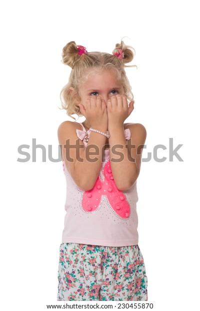 Upset little blonde girl on a white background