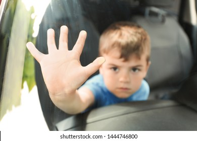 Upset little boy closed inside car, closeup with space for text. Child in danger
