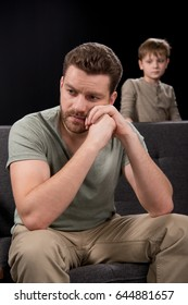 Upset little boy looking at pensive father sitting on sofa and looking away, family problems concept