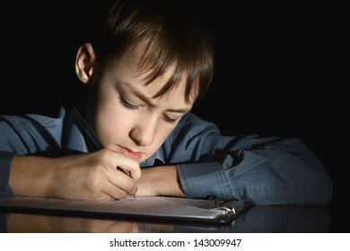 upset little boy on a black background