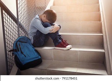 Upset little boy sitting on stairs indoors