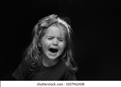 Upset little girl crying out load, balck and white portrait isolated on black