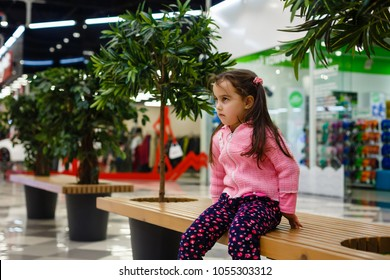 Upset little lost girl sitting on bench in mall