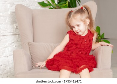 upset little three year old girl in a red dress sitting in a chair
