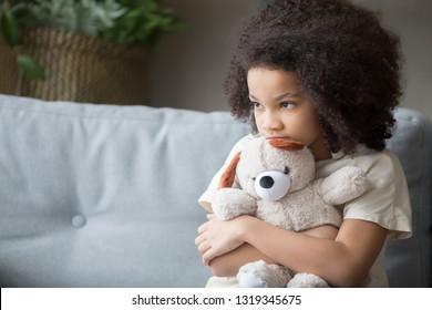 Upset lonely bullied little african american kid girl holding teddy bear looking away feels abandoned abused, sad alone preschool mixed race child orphan hugging stuffed toy, charity adoption concept