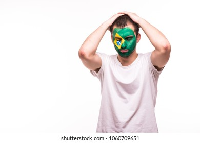 Upset loser fan support of Brazil national team with painted face isolated on white