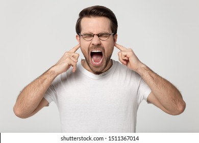 Upset mad stressed millennial guy in eyewear, plugging ears with fingers, shouting, screaming, yelling, annoyed by loud unpleasant sound or noisy neighbors, isolated on grey white studio background.
