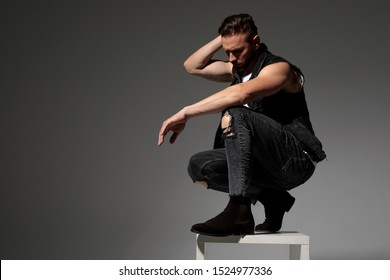 Upset man holding his hand on his neck and leaning on his knee while squatting on a chair and wearing a black jeans vest on gray studio background