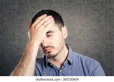 Upset man holding his head