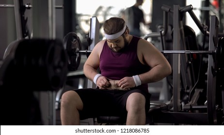 Upset man looking at his fat stomach, desire to lose weight, sport gym workout
