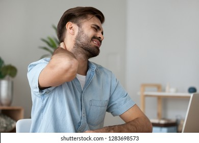 Upset man in pain touching stiff neck suffering from fibromyalgia massaging tensed muscles to relieve back joint shoulder ache tired after long sedentary computer work in incorrect posture concept