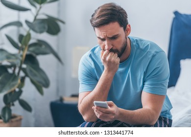 upset man sitting on bed, covering mouth with hand and using smartphone at home